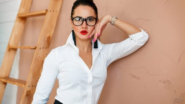 Деловая женщина в очках у стены