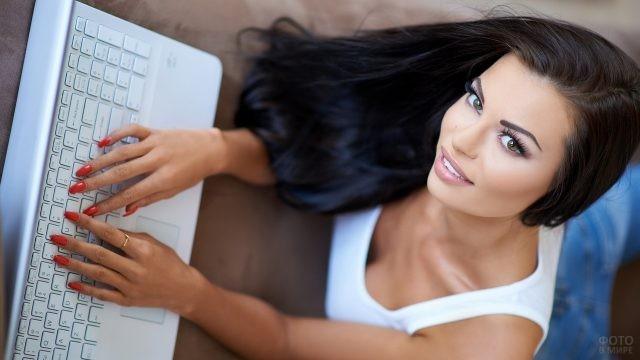 Девушка пишет на белом ноутбуке