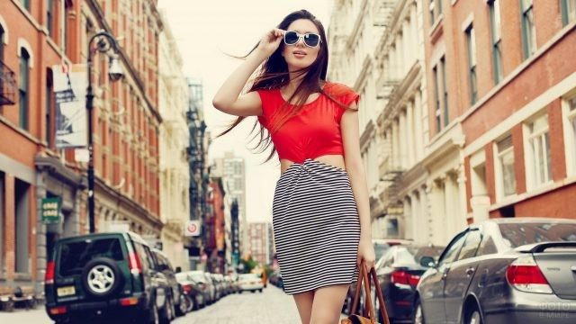 Девушка в солнцезащитных очках идёт по городской дороге