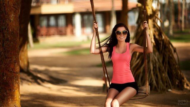 Девушка в солнцезащитных очках на качелях