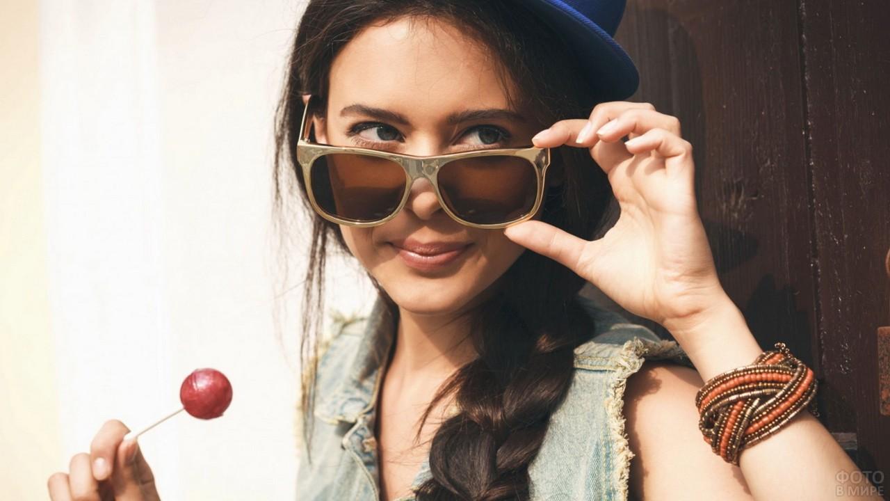 Девушка в солнцезащитных очках с чупа-чупсом