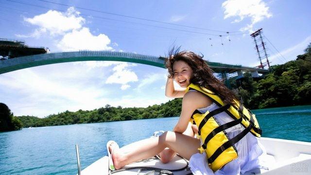 Девушка в спасательном жилете на корпусе катера