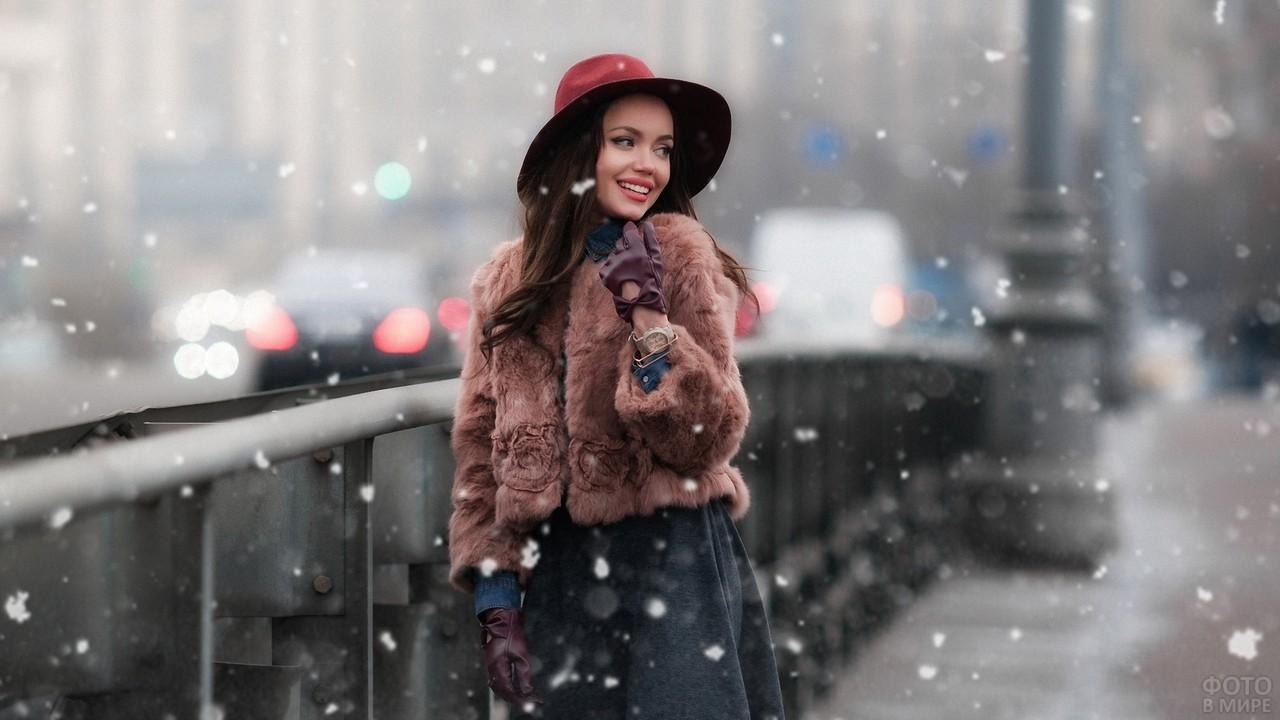 Кокетливая девушка в шубке и шляпе на набережной