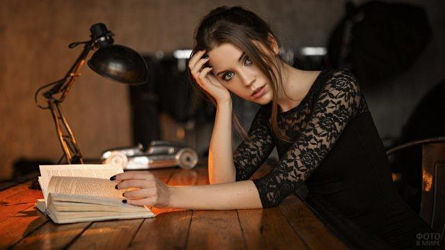 Ксения Кокорева за столом читает под светом лампы