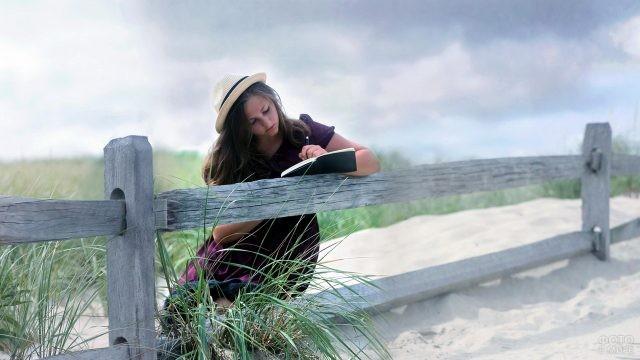 Пишущая девушка облокотилась на забор