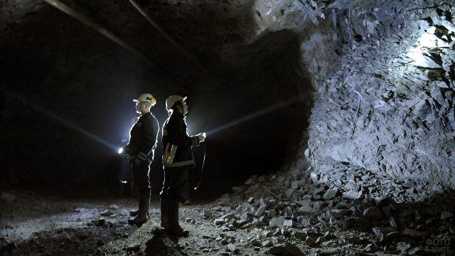 Двое мужчин с фонариками в шахте