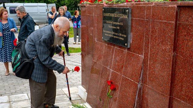 Пенсионер возлагает цветы к мемориалу шахтёрам в Сланцах