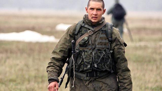 Молодой десантник шагает через поле