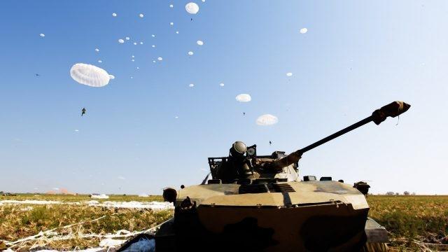 Парашюты десантников на фоне ясного неба над БМП в поле