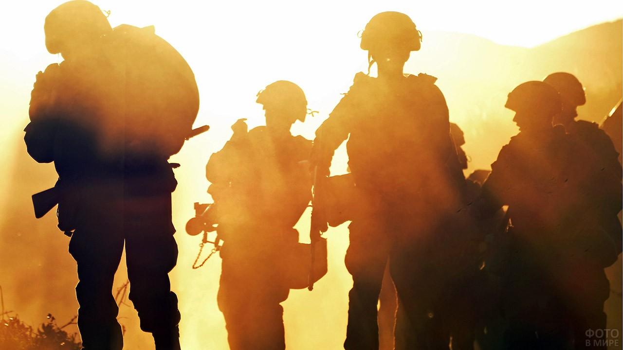 Силуэты десантников на фоне лучей вечернего солнца