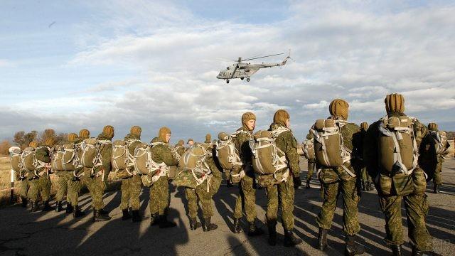 Вертолёт над парашютистами-десантниками на лётном поле