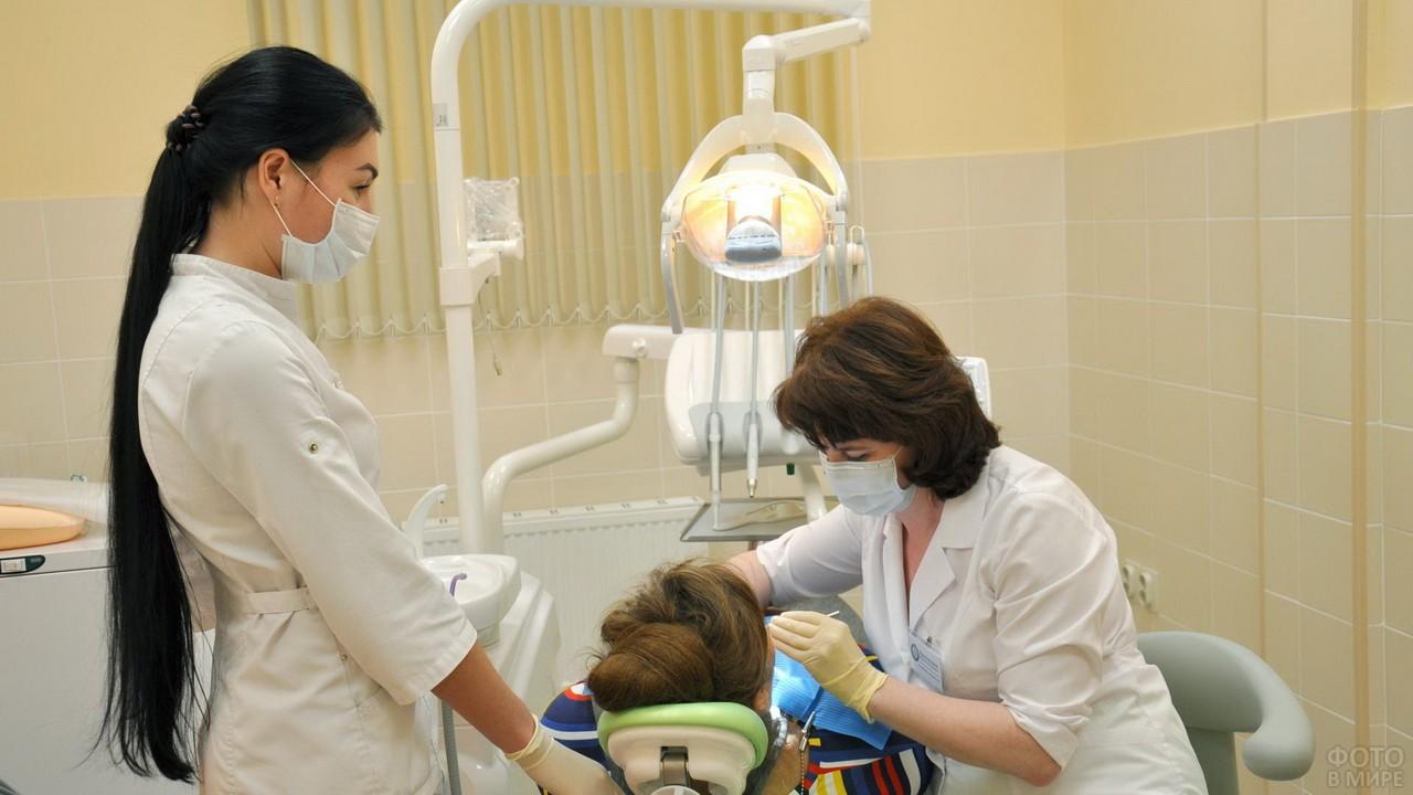 Ассистентка стоматолога возле пациента