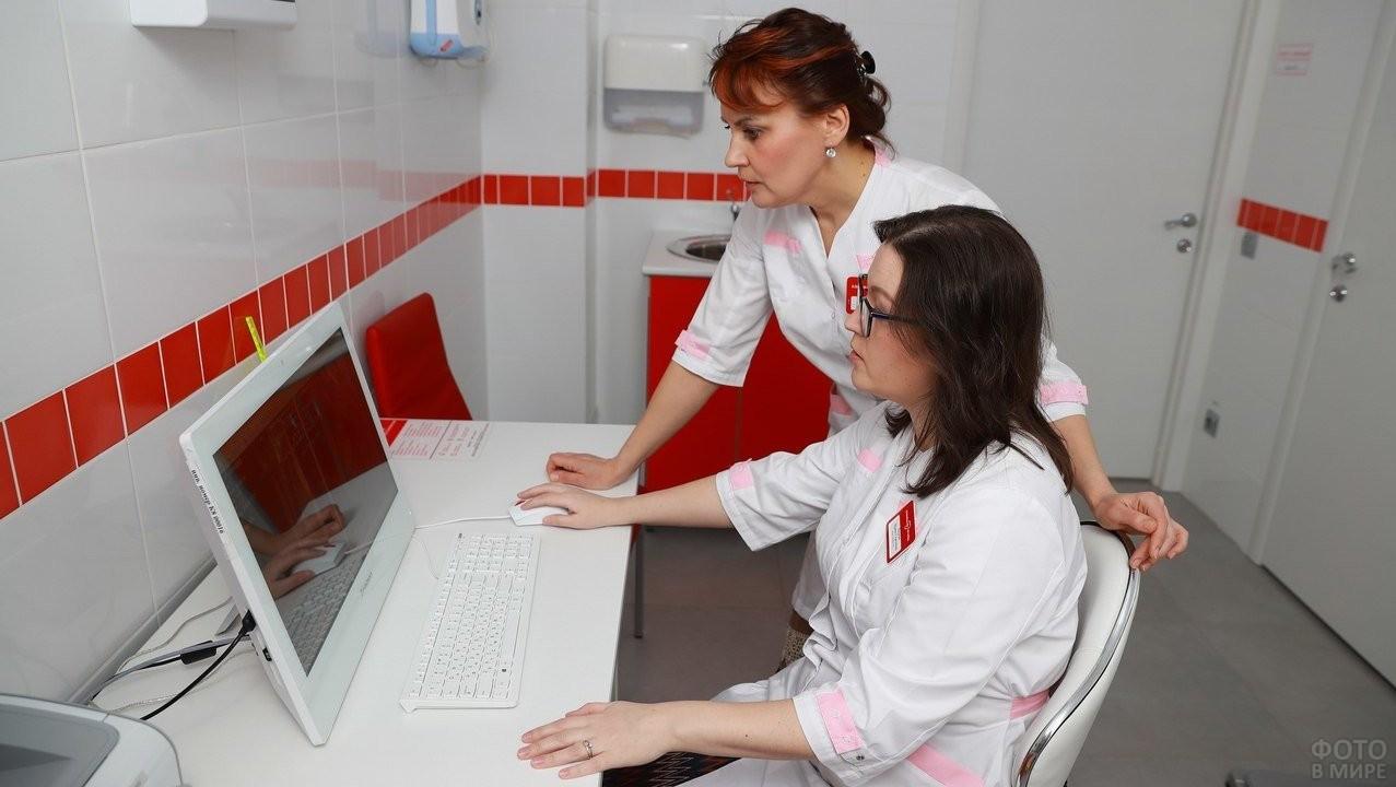 Две коллеги смотрят в монитор компьютера