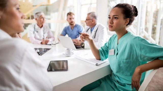 Консилиум медперсонала за белым столом
