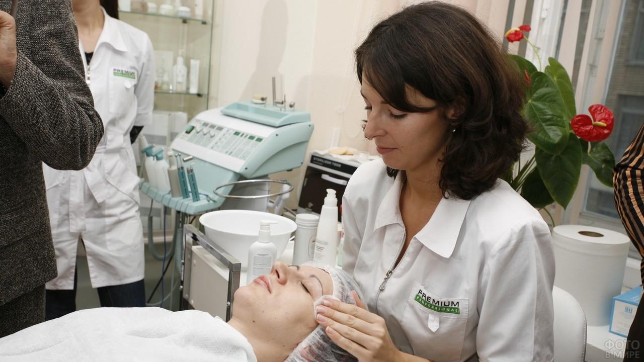 Косметолог протирает клиенту лицо