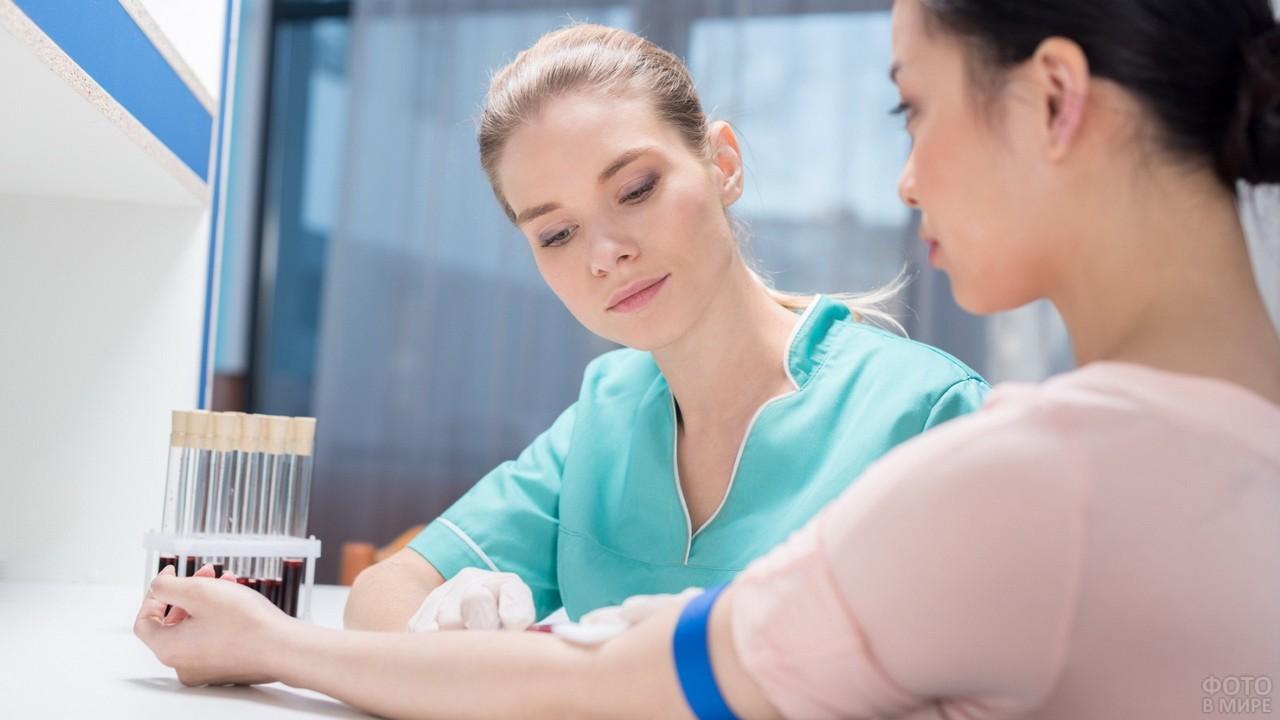 Медицинский работник берёт кровь из вены