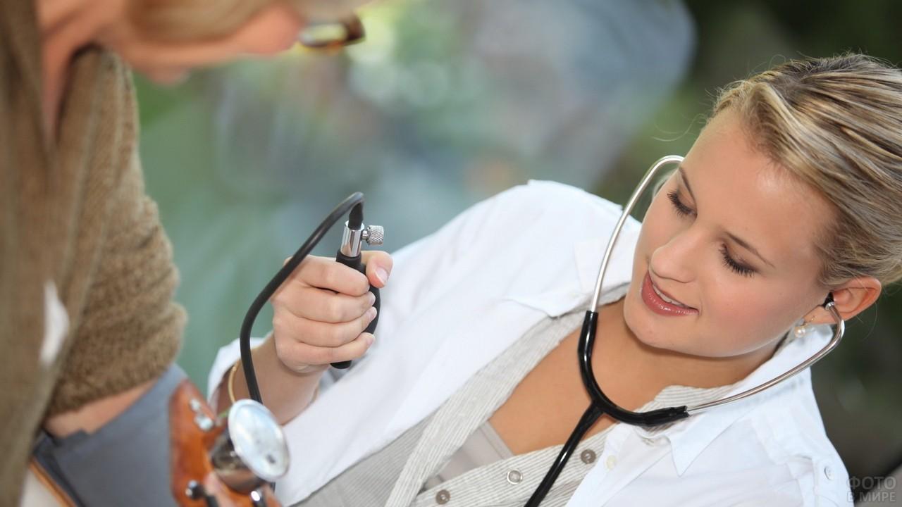 Медсестра измеряет давление