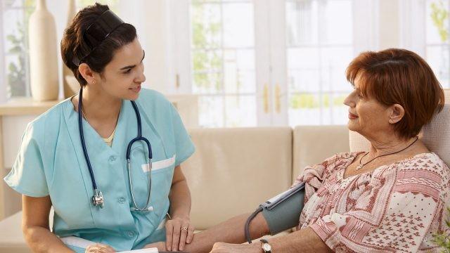 Медсестра меряет давление женщине