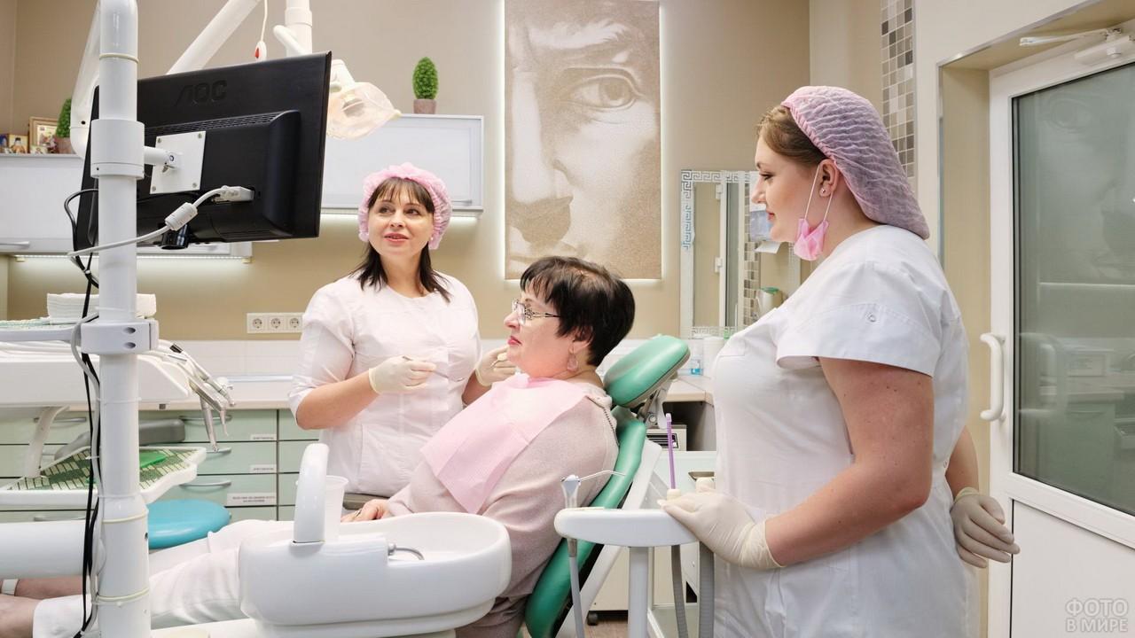 Медсестра рядом с пациентом и стоматологом