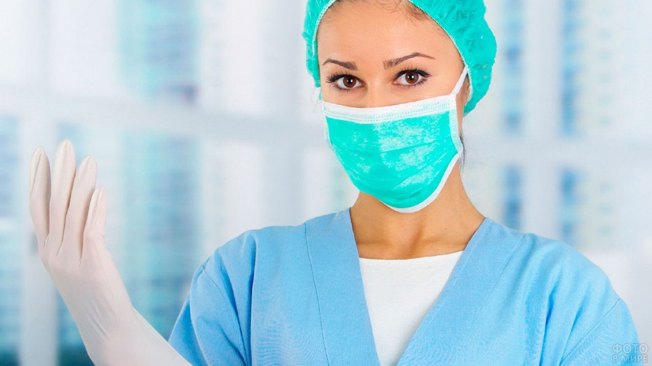 Медсестра в маске надевает перчатки