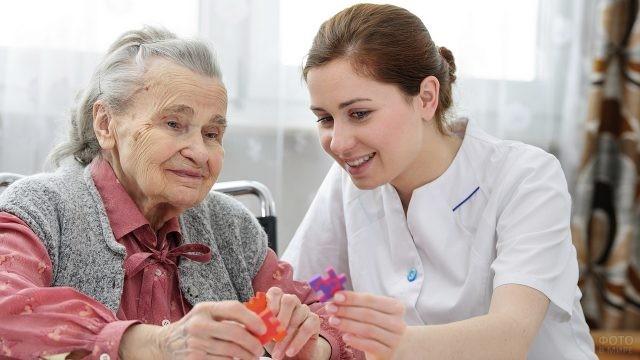 Милая медсестра общается с бабушкой