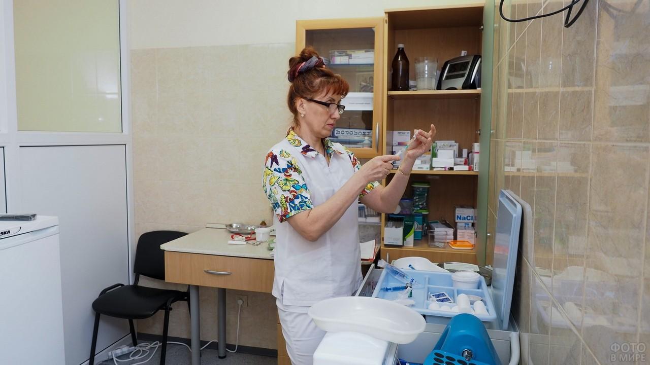 Работник набирает шприц лекарством