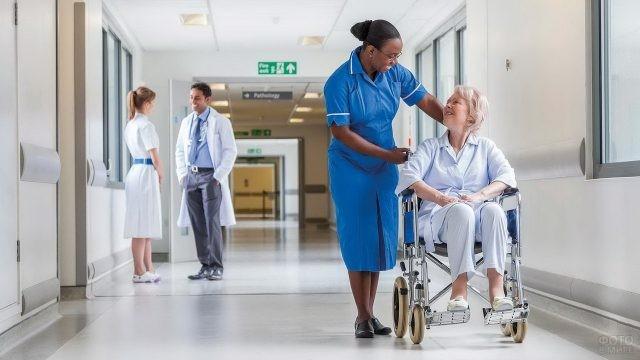 Темнокожая сотрудница катит коляску с пациентом