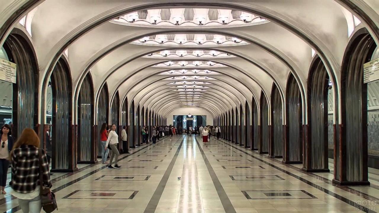 Люди выходят из поезда на станции