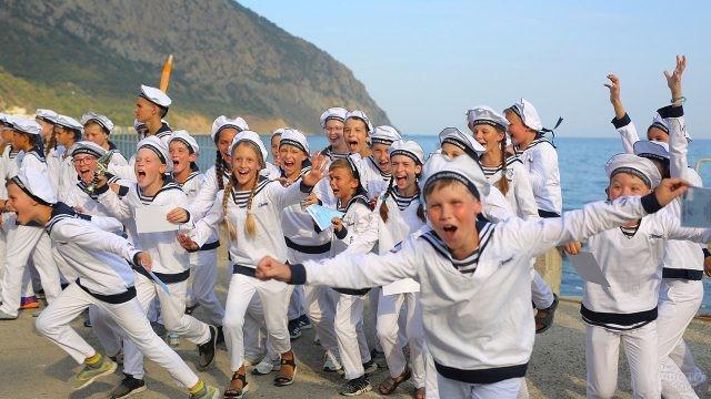 Малыши в матросках бегут по пляжу