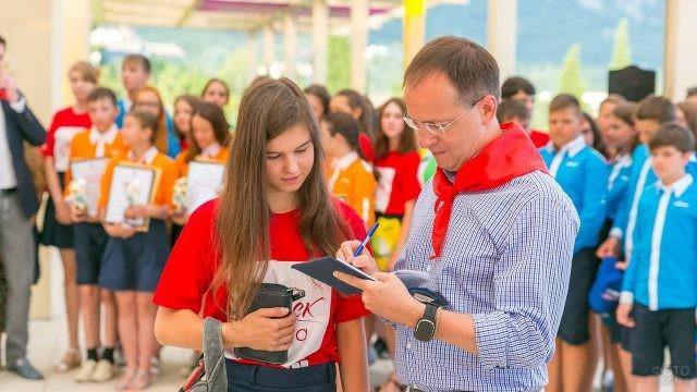 Министр культуры даёт автограф отдыхающей в лагере школьнице