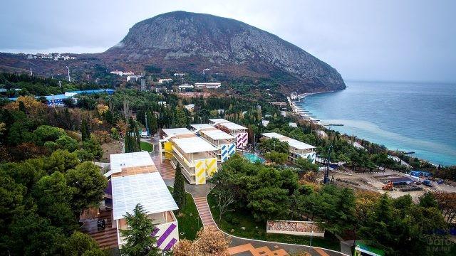 Разноцветные жилые корпуса на панораме парка над морем