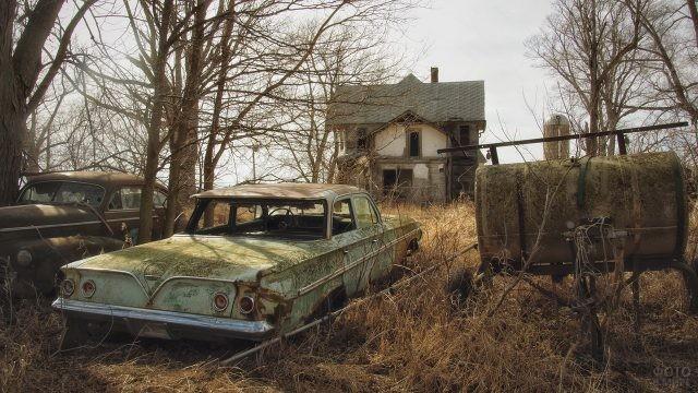 Ржавые машины на фоне старого дома