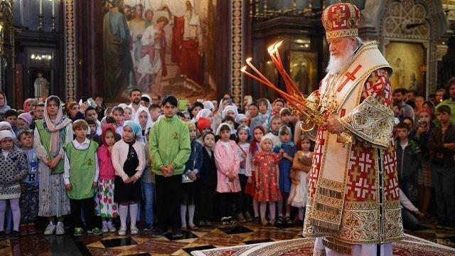 Патриарх и ученики воскресной школы во время службы
