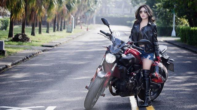 Азиатка на мотоцикле на дороге