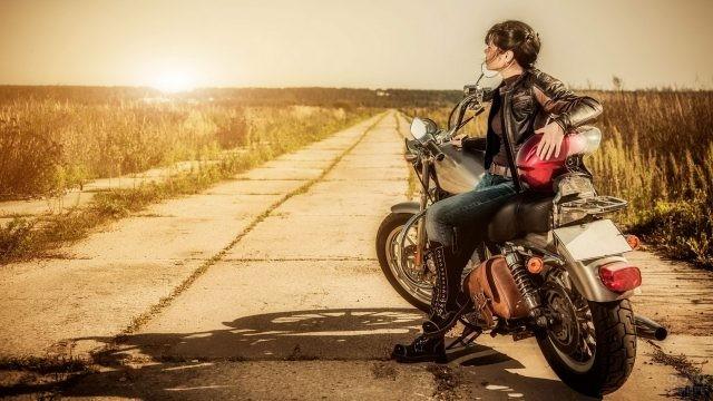 Девушка на мотоцикле смотрит на закат