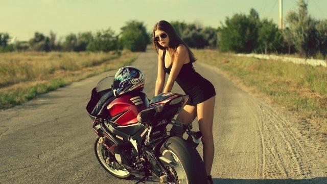 Девушка возле мотоцикла за городом