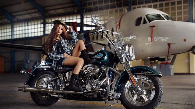 Кудрявая девушка с мотоциклом в ангаре