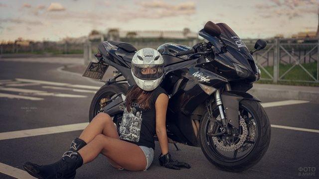 Русая девушка в шлеме на асфальте
