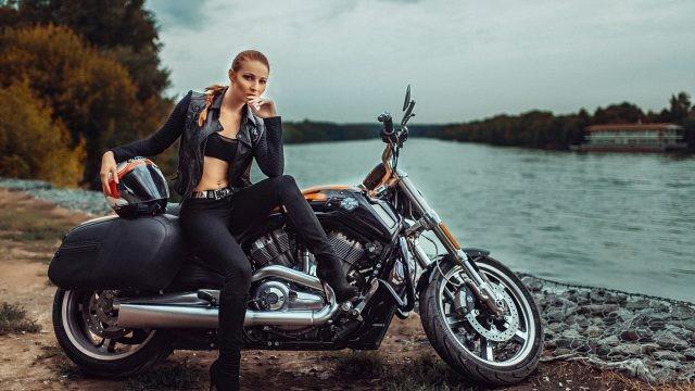 Рыжая девушка на мотоцикле у водоёма