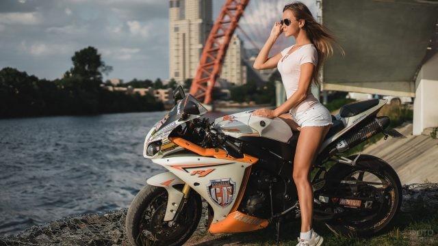 Стройная девушка на мотоцикле у водоёма