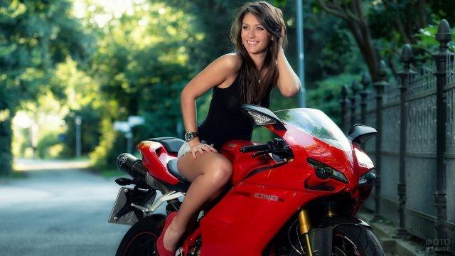 Улыбающаяся девушка на красном мотоцикле