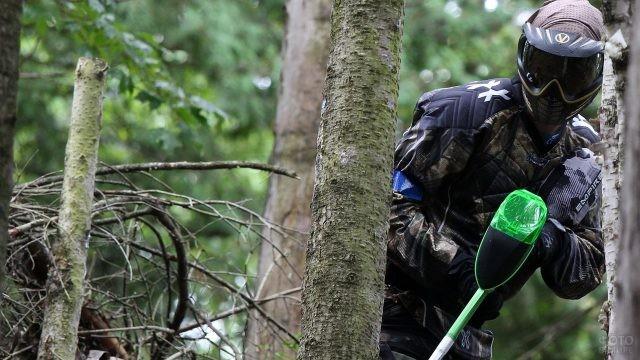 Парень прячется за деревьями