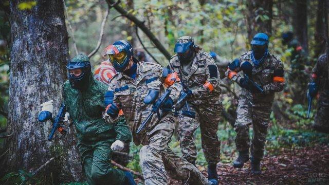 Пейнтбольная команда бежит по лесу