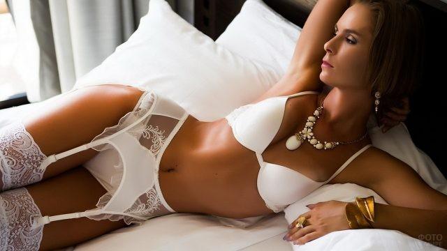 Девушка в белом наряде на постели