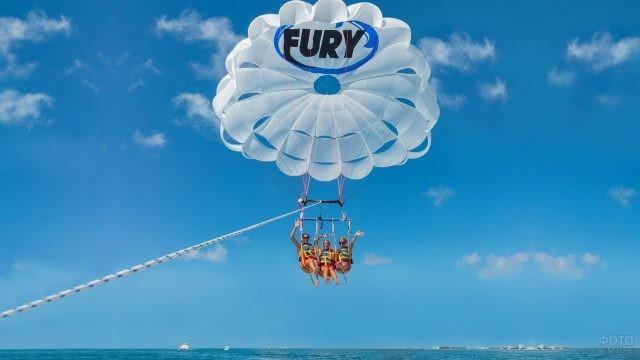 Туристы на парашюте над морем