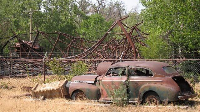 Арматура от американских горок возле старого автомобиля