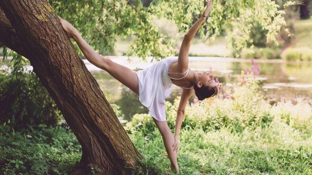 Балерина у дерева возле водоёма
