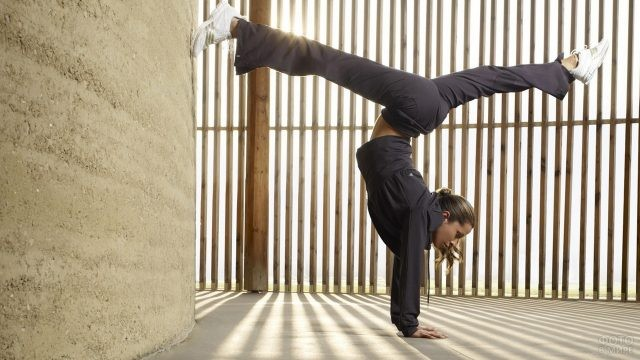 Девушка в спортивном костюме вверх ногами