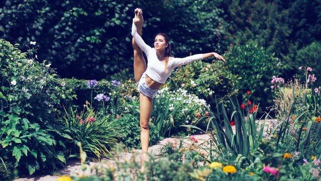 Гибкая девушка на одной ноге в саду