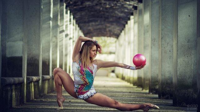 Гибкая девушка с мячом в руке